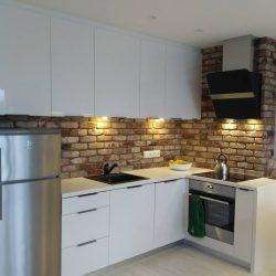 aneks kuchenny biały połysk, cegła na ścianie
